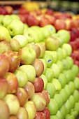 Various types of apples, in piles, in a supermarket