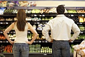 Couple standing thoughtfully in supermarket vegetable section