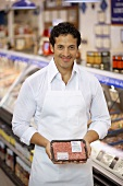 Butcher showing pack of mince in a supermarket