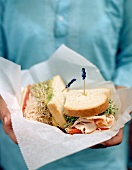 Person holding club sandwich with sprouts on sandwich wrap