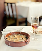 Baked sorrel and mushroom dish and glass of wine on table