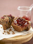 Cranberry bran muffin, halved, with strawberry jam