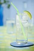 Glass of water with lime wedge, ice cubes and straw