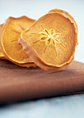 Dried Sharon fruit slices on chopping board