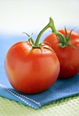Two fresh vine tomatoes on blue cloth