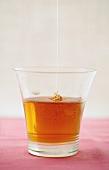 Honey trickling into a glass