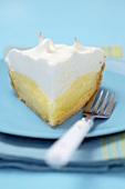 Piece of lemon meringue pie on blue plate with fork (USA)