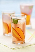 Three glasses of iced tea with peach slices on napkin