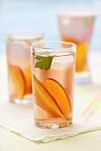Three glasses of iced tea with peach slices on napkin