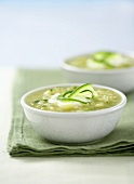 Courgette soup in two bowls on green fabric napkin