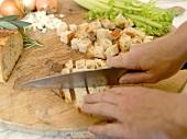 Hands dicing bread