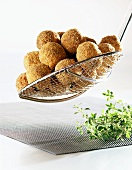 Deep-fried fish balls on straining spoon