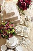 Three-tiered white wedding cake, flowers and tea set