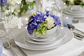Festive place-setting for wedding with flowers in soup bowl