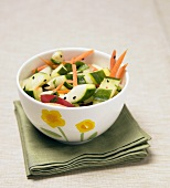 Cucumber salad with carrots in bowl on green napkin
