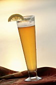 Large glass of light wheat beer with lemon wedge outdoors