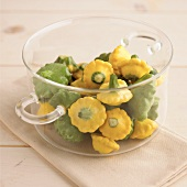 Green and yellow baby patty pan squashes in glass bowl