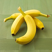 Three bananas on a green background