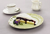 Slice of Layered Cake with Blueberry Filling on a Plate, Tea Cup and Pitcher