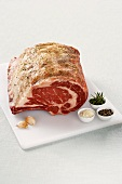 Rib Roast on a Cutting Board with Garlic and Herbs, White Background