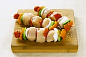 Uncooked Chicken and Vegetable Kabobs on a Cutting Board