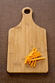 Cutting Board with a Pile of Carrot Sticks