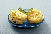 Two Fettuccini Noodle Nests on a Blue Plate
