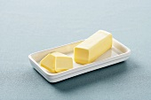 Partially Sliced Stick of Butter on White Butter Dish