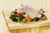 Whole Chicken on a Cutting Board with Spices and Vegetables
