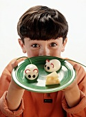 Boy Holding a Plate with Two Boiled Egg Mice and a Wedge of Swiss Cheese