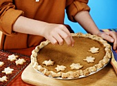Child Placing Leaf Shaped Pie Crust Cut Outs on the Top of a Pumpkin Pie