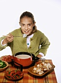 Girl About to Eat Bread Dipped in Cheese Fondue, Fondue Pot with Cheese Fondue, Bread and Vegetables