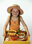 Young Girl with Long Braids Holding a Tray with Three Bowls of Assorted Fresh Salsas