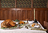 Roast Turkey on a Platter on a Table with Side Dishes, Place Setting