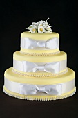 Three Tiered Yellow Cake with White Ribbon Wrapped Around Each Tier, Black Background