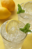 Lemonade Over Ice in Two Tumbler Glasses with Lemon Slices and Mint, Lemons