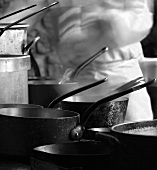 A Variety of Saucepans with Chef in Background