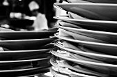 Close up of Stacked Plates in a Kitchen with Chef in Background