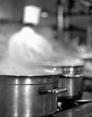 Dampfende Töpfe am Herd in Grossküche, Koch im Hintergrund