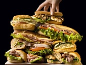 A Hand Adding to a Large Stack of Sandwiches