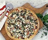 Gemüsepizza mit Pilzen und Schafskäse auf Holzbrett