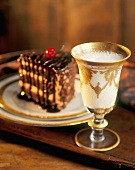 Glass of Milk in a Gold Trim Glass; with Chocolate Cake in Background
