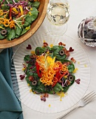 Spinach Salad on a Glass Plate and in Serving Bowl; From Above; Glass of White Wine