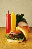Hamburger on Table with Ketchup and Mustard Bottles