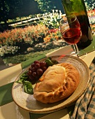 Calzone on a Plate with Wine; Country Setting