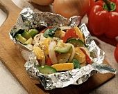 Grilled Vegetables in Foil Packet on a Wooden Board
