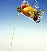 Pouring Juice out of a Pitcher with Fresh Fruits