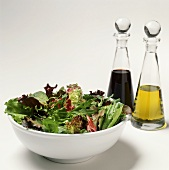 Mixed Green Salad with Bottles of Oil and Vinegar