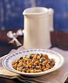 Knusper-Flakes mit Heidelbeeren, dahinter ein Milchkrug