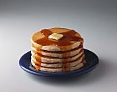 Ein Stapel Pancakes mit Ahornsirup & Butter auf Teller